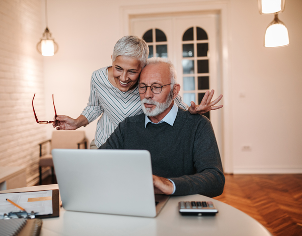 couple senior souriant devant laptop
